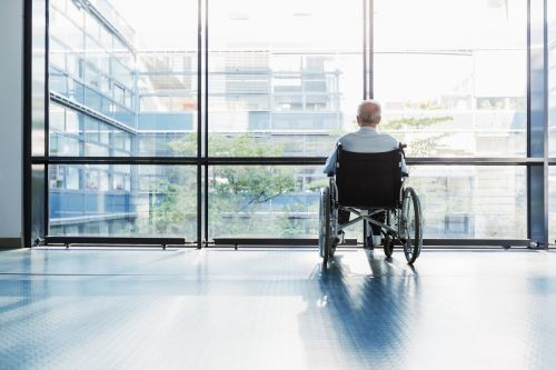 Senior Man in Wheelchair looking out of a window in a hospital corridor. - The Robenalt Law Firm, Inc.