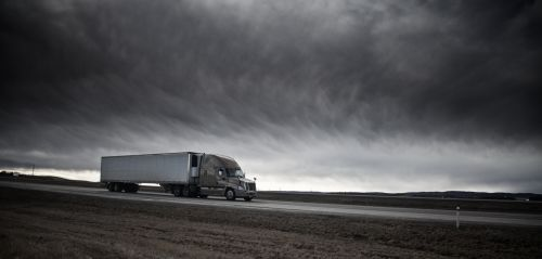 Side view of a semi-truck speeding down the highway with dark clouds - The Robenalt Law Firm, Inc.
