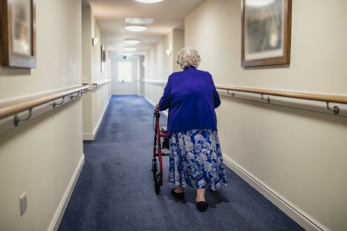 A senior woman walking down a corridor with the assistance of a walker - The Robenalt Law Firm, Inc.
