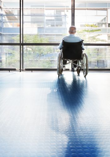 Senior man in a wheelchair looking out of a window in a hospital corridor.