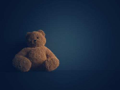 Teddy bear with torn eye sits in dark room - The Robenalt Law Firm, Inc.