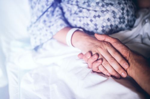 Holding Hands in Hospital Bed - Proper Elder Care Concept