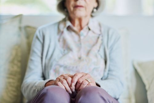 Senior woman sitting on a sofa alone