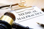 Clipboard with documents about medical malpractice and gavel - The Robenalt Law Firm, Inc.