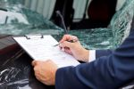 insurance assessor inspecting damaged vehicle