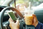 Driving while holding ice coffee and texting